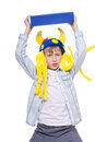 Cute angry stylish child wearing funny hat holding a very big blue book above with menacing look isolated on white background Royalty Free Stock Photos