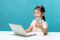 Cute asia little girl is sitting at table with her white laptop and a smartphones, isolated over blue Royalty Free Stock Photo