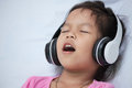 Cute asian child girl in headphones listening the music Royalty Free Stock Photo