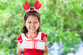 Cute asian child girl holding Christmas gift in hand Royalty Free Stock Photo