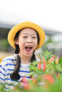 Cute Asian ittle girl sitting with vegetable plot Royalty Free Stock Photo