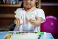 Cute asian little girl is trying to connect couple jigsaw puzzle Royalty Free Stock Photo