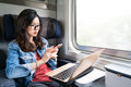 Cute Asian woman using smartphone and laptop on train, copy space on window, business travel or technology concept Royalty Free Stock Photo