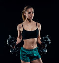 Cute athletic model girl in sportswear with dumbbells in studio against black background. Ideal female sports figure. Royalty Free Stock Photo
