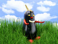 Cute aubergine puppet outdoor on green meadow with a nice blue sky and pretty clouds Royalty Free Stock Image