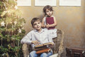 Cute babies boy and girl in a chair reading a book in a interior Royalty Free Stock Photo