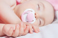 Cute baby asleep in bed hands in focus in the foreground close up Royalty Free Stock Photo