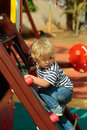 Cute baby boy climbing rope net or ladder Royalty Free Stock Photo