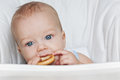 Cute baby boy eating a bagel at table on white background Royalty Free Stock Photo