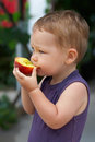 Cute baby boy eating fresh fruit outdoors Royalty Free Stock Photography