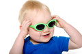 Cute baby boy with green sunglasses month old blond hair and blue shirt wearing on white background Royalty Free Stock Image