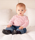 Cute baby boy in jeans and striped t shirt sitting on a bed Stock Photo