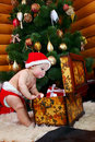 Cute baby boy looking into case with gifts Stock Image