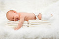 Cute baby boy lying on stack of towels full length side view newborn relaxing fur blanket Stock Photo