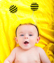 Cute baby boy lying on a yellow scarf Stock Images