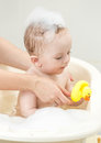 Cute baby boy playing in foam bath with yellow rubber duck Royalty Free Stock Photo