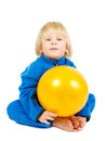 Cute baby boy plays with yellow ball sits on a floor and Royalty Free Stock Photos