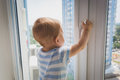 Cute baby boy pulling by the window handle. Concept of child in Royalty Free Stock Photo