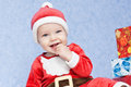 Cute baby boy santa helper on a blue background Stock Photo