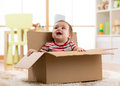 Cute baby boy sitting inside brown cardboard box Royalty Free Stock Photo