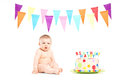 Cute baby boy sitting next to a birthday cake and party flags isolated on white Royalty Free Stock Photo