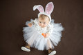 Cute baby with carrot on brown Royalty Free Stock Images