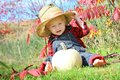 Cute baby country boy in autumn a is sitting outside the grass with a white pumpkin on a sunny day wearing a straw hat flannel and Royalty Free Stock Photos