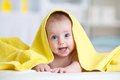 Cute baby covered with a bath towel lying on tummy in the bathroom Royalty Free Stock Photo