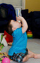 Cute baby drinking from a bottle by himself Royalty Free Stock Images