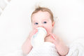Cute baby drinking milk from a bottle in a white crib Royalty Free Stock Photo