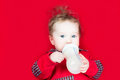 Cute baby drinking milk on a red blanket Royalty Free Stock Photo