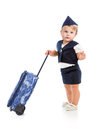 Cute baby girl dressed as stewardess with trunk