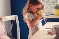 Cute baby girl drinking tea for breakfast in sunny kitchen