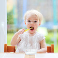Cute baby girl eating yogurt from spoon Royalty Free Stock Photo