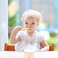 Cute baby girl eating yogurt from spoon Royalty Free Stock Photo
