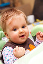 Cute baby girl in high chair Stock Photo