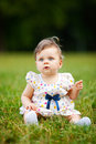 Cute baby girl image of adorable sitting on grass shallow depth of field Royalty Free Stock Photography