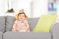 Cute baby girl with a knitted hat sitting on sofa at home Stock Photography