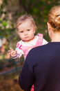 Cute baby girl looking out from mother's back Royalty Free Stock Photo