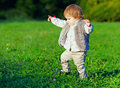 Cute baby girl making first steps outdoors colorful Stock Photography