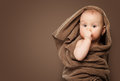 Cute baby girl months in a brown blanket sucking thumb Stock Photo