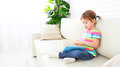 Cute baby girl reading book at home sitting on sofa Royalty Free Stock Photo