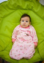 Cute baby girl sitting on chair dressed in pajamas Royalty Free Stock Photo
