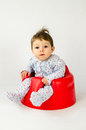 Cute baby girl sitting in a plastic seat Royalty Free Stock Photo