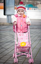 Cute baby girl with toy stroller outside Royalty Free Stock Image