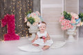 Cute baby girl 1-2 year old sitting on floor with pink balloons in room over white. Isolated. Birthday party. Celebration. Happy b Royalty Free Stock Photo