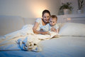 Cute baby and his mother playing with toy on bed before going to Royalty Free Stock Photo