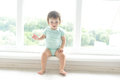 Cute baby at home in white room is sitting near window. The beautiful baby could be a boy or girl and is wearing body suit.