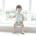 Cute baby at home in white room is sitting near window. The beautiful baby could be a boy or girl and is wearing body suit. Royalty Free Stock Photo