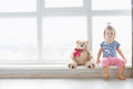 Cute baby at home in white room is sitting near window. The beautiful baby girl with teddy bear. Royalty Free Stock Photo